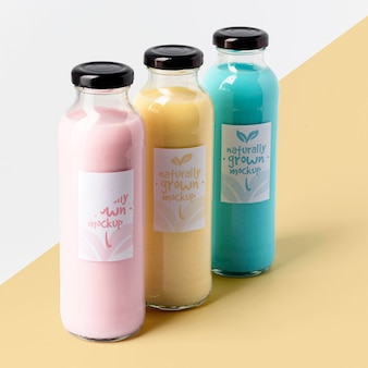 Alto angolo di assortimento di bottiglie di succo trasparenti