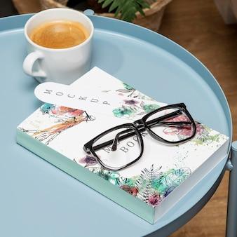 メガネとブックマークのコーヒーテーブルの上の高角度の本のモックアップ