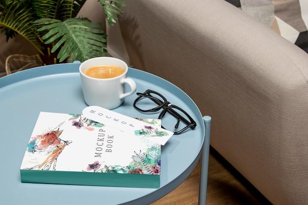 メガネとコーヒーテーブルの上の高角度の本のモックアップ