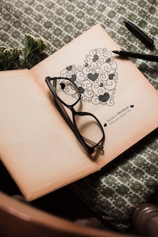 High angle of book with glasses and pen