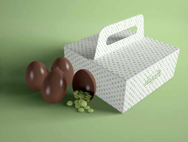 High angle box with chocolate eggs beside