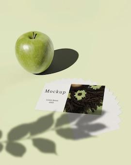 Alto angolo della carta con l'ombra delle foglie e della mela