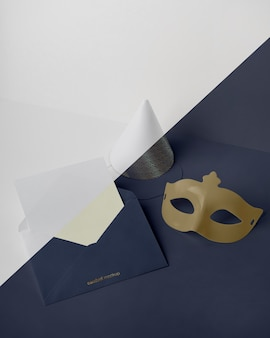 High angle of carnival invitation in envelope with cone and mask