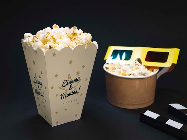 High angle of cinema glasses with popcorn and clapperboard