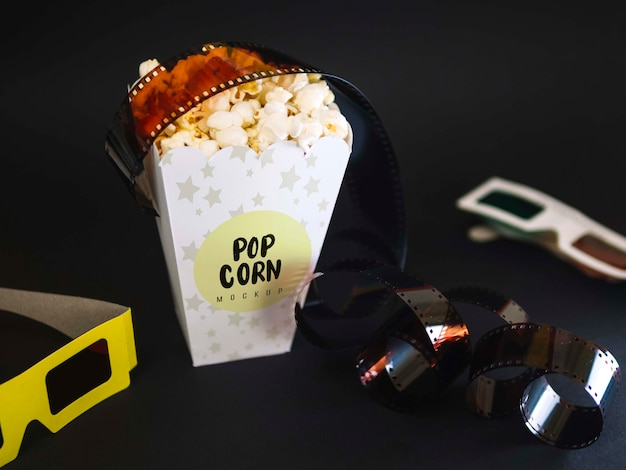 High angle of cinema glasses with popcorn and film