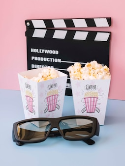 High angle of clapperboard with cinema popcorn and glasses