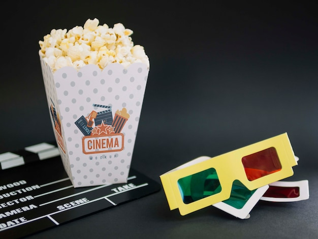 High angle of cup with popcorn and cinema glasses