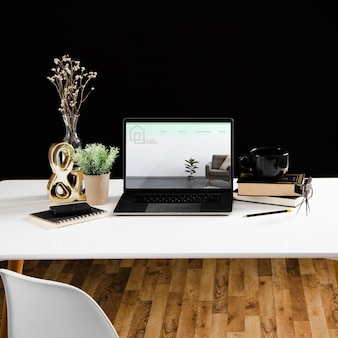 High angle of desk with laptop and notebook
