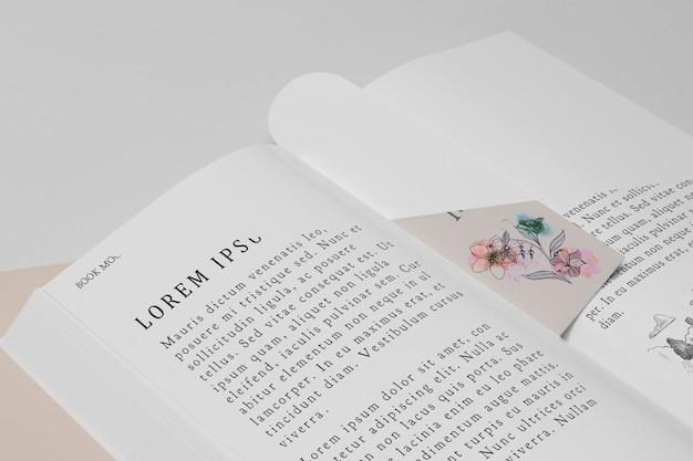 高角度の花のブックマークと開いた本のモックアップ