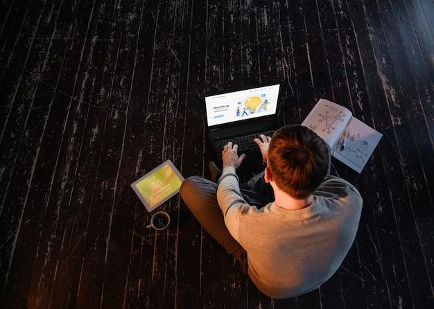 Angolo alto dell'uomo che lavora dalla casa sul computer portatile con lo spazio della copia e del caffè