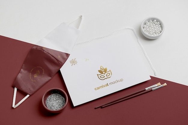 High angle of minimalistic carnival invitation with beads and face mask