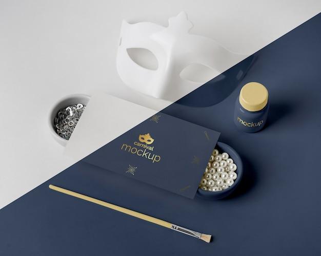 Alto angolo di invito di carnevale minimalista con maschera e assortimento di perline