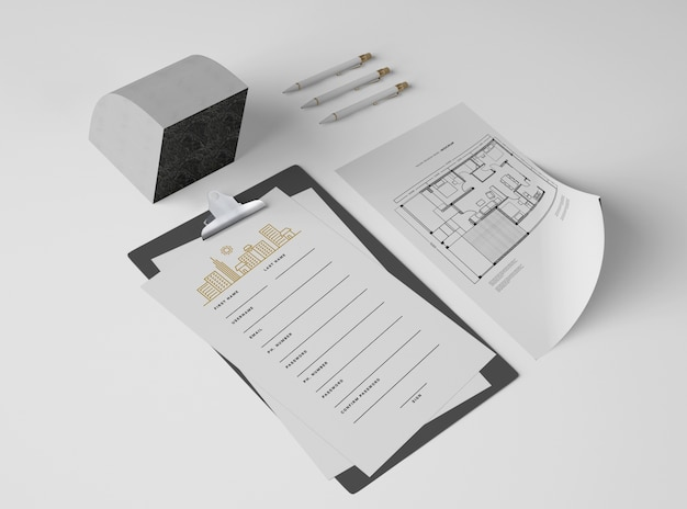 High angle of notepad with papers and plan