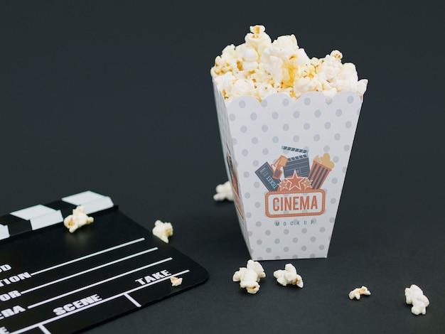 Высокий угол чашки с попкорном и хлопушкой для кино