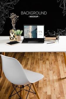 Высокий угол стола с ноутбуком и стулом