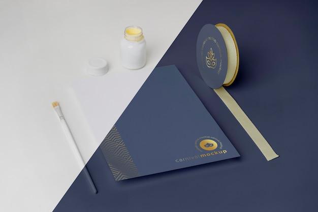 テープとペイントブラシでミニマルなカーニバルの招待状の高角度