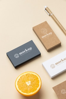 High angle of paper stationery with citrus and pen