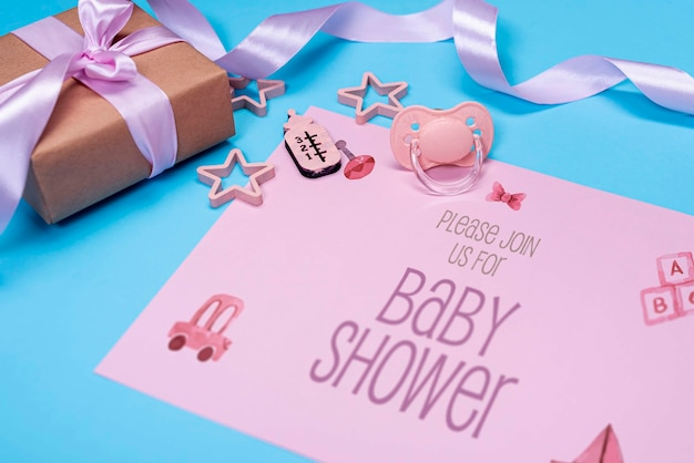 High angle of pink baby invitation with gift