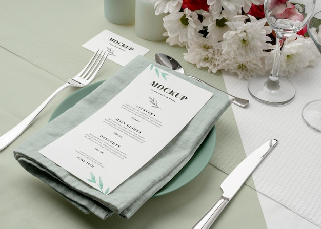 High angle of spring menu mock-up on plate with cutlery and flowers
