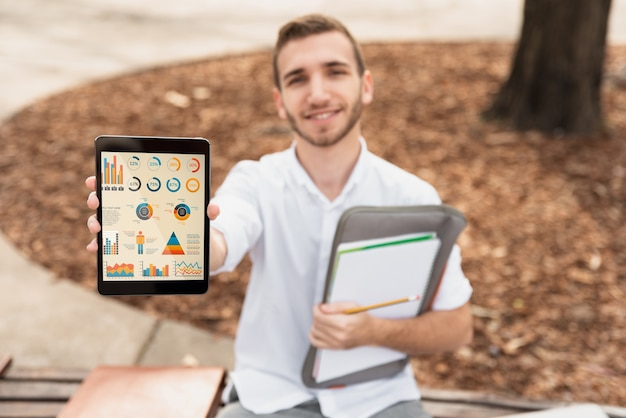 High angle university male holding tablet