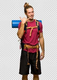 Hiker man with mountain backpacker making phone gesture. call me back sign