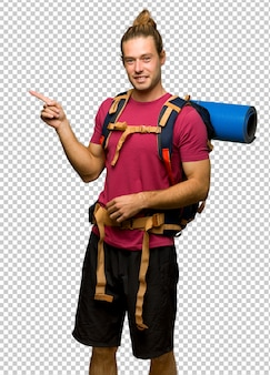 Hiker man with mountain backpacker pointing finger to the side in lateral position