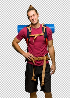 Hiker man with mountain backpacker posing with arms at hip and smiling