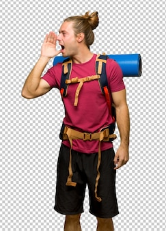 Hiker man with mountain backpacker shouting with mouth wide open to the lateral