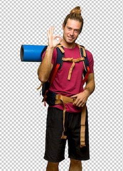 Hiker man with mountain backpacker showing an ok sign with fingers