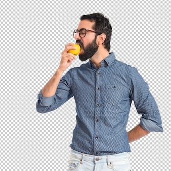 若いhipster男リンゴを食べる、白い背景