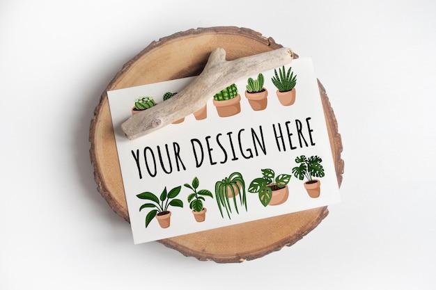白いテーブルの上の木製のカットツリーセクションにはがきのモックアップします。白いテーブルにはがきの自由ho放に生きるデザイン