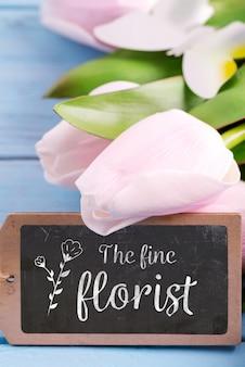 Поздравительная открытка с рамкой из свежих нежных тюльпанов и доской для сообщения