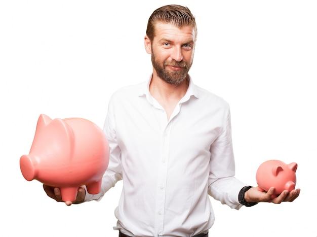 Hombre de negocios que sostiene dos huchas de diferentes tamaños