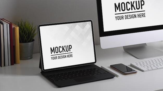 Рабочий стол домашнего офиса с компьютером, планшетом, макетом расходных материалов и украшением