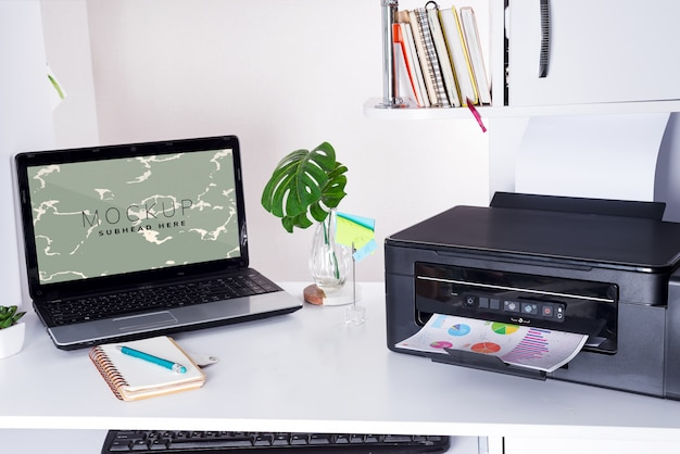 Home office desk with laptop, leaves and printer