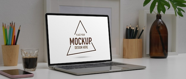 Home office desk with mockup laptop, smartphone, stationery and decorations