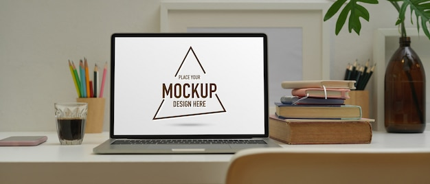 Home office desk with mockup laptop, stationery, books and decorations in modern room