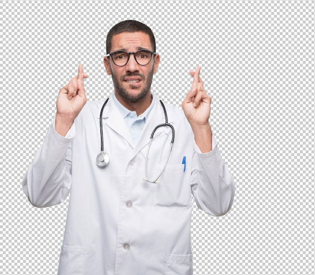 Hopeful young doctor with crossed fingers gesture