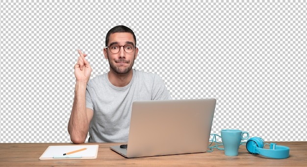 Hopeful young man sitting at his desk with crossed fingers gesture