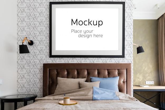 スタイリッシュなインテリアの壁に木製フレームの水平ポスターモックアップ。寝室のヘッドボードの後ろの壁にその内部に空きスペースがある段ボールのパスパルト。