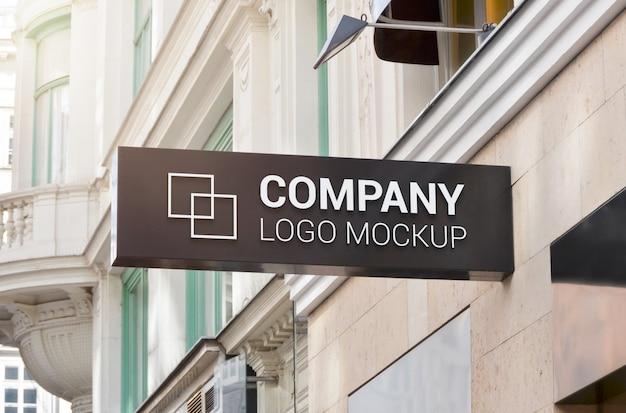 Horizontal rectangle sign company logo mockup on building wall.