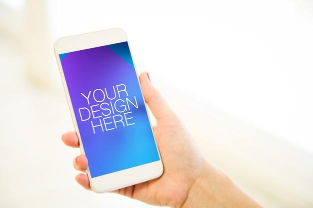 人間のスマートフォンのモックアップを保持