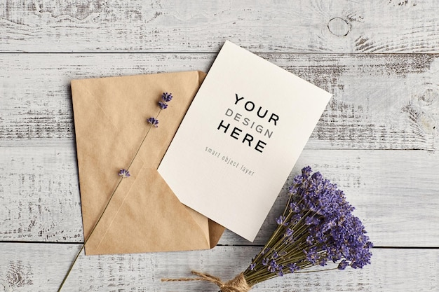 Invitation card mockup with envelope and lavender flowers bouquet on wooden background