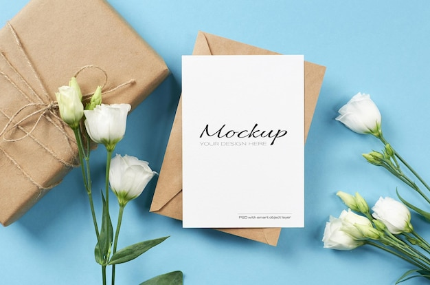 Invitation card mockup with white eustoma flowers and gift box on blue background
