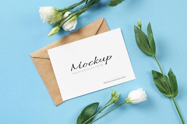 파란색 종이 배경에 흰색 eustoma 꽃과 초대 카드 모형