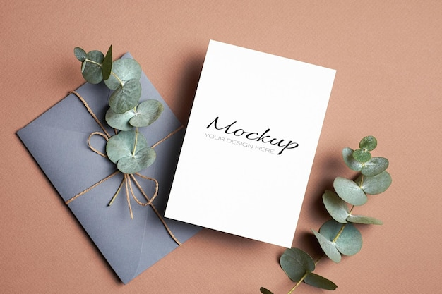 Invitation or greeting card mockup with envelope and eucalyptus twig
