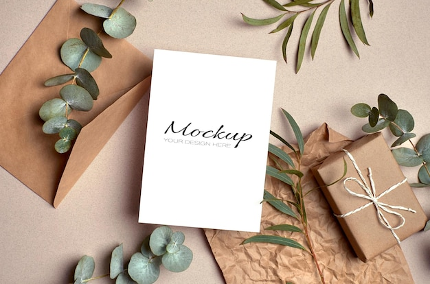 Invitation or greeting card mockup with envelope, gift box and green eucalyptus twigs