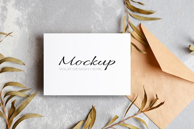 Invitation or greeting card mockup with envelope and gold eucalyptus twigs