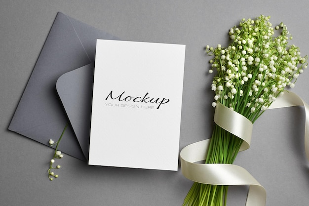 Invitation or greeting card mockup with envelope and lily of the valley flowers bouquet with ribbon