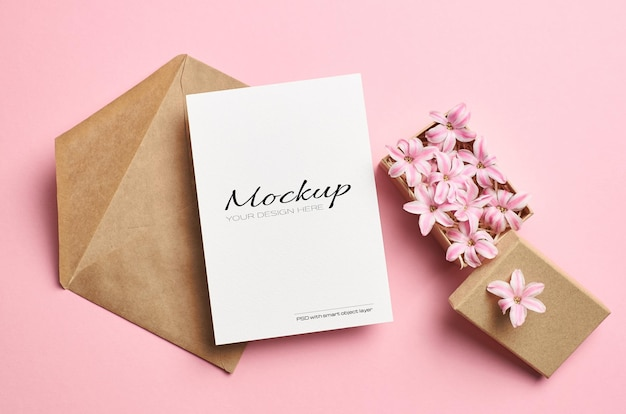Invitation or greeting card mockup with envelope and pink flowers in box